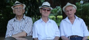 3 happy old men sitting on a bench because they got a reverse mortgage in Waddell